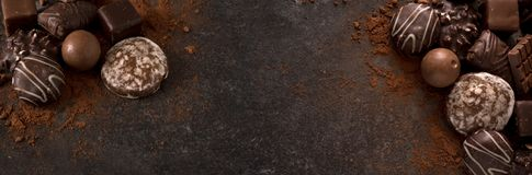 chocolate cookies and pralines for a holiday event on a dark slate background with large copy space, wide panoramic banner format stock photography