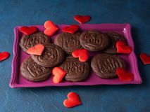 Chocolate cookies for Valentine`s day. Chocolate cookies spelling For you as home made gift for Valentine`s day over blue background Stock Photo