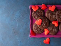 Chocolate cookies for Valentine`s day. Chocolate cookies spelling For you as home made gift for Valentine`s day over blue background Royalty Free Stock Photos