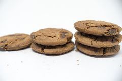 Chocolate cookies on a white background. A cookie is a baked or cooked food that is small, flat and sweet. It usually contains flour, sugar and some type of stock image