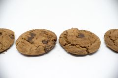 Chocolate cookies on a white background. A cookie is a baked or cooked food that is small, flat and sweet. It usually contains flour, sugar and some type of Stock Photo