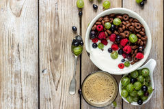 Chocolate cornflakes with berries. Yogurt and coffee for breakfast. Top view Stock Images