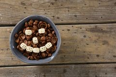 Chocolate cornflakes with honeycomb cereal forming smiley face in bowl Royalty Free Stock Images