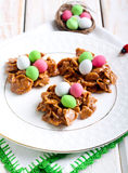 Chocolate and cornflakes nests with candy eggs Stock Photography