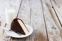 Chocolate-cottage cheese cake and milk on wooden background. Royalty Free Stock Photography