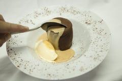 Chocolate coulant com o gelado de baunilha que está sendo começado pela colher fotografia de stock