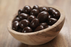 Chocolate covered almonds in wood bowl on table Royalty Free Stock Photography