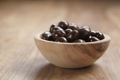 Chocolate covered almonds in wood bowl on table Royalty Free Stock Images