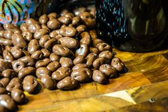 Chocolate Covered Coffee Beans with Coffee Mug up close. Chocolate Covered Coffee Beans on a solid wood cutting board in the kitchen with a coffee mug up close stock photos