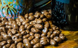 Chocolate Covered Coffee Beans with Coffee Mug up close. Chocolate Covered Coffee Beans on a solid wood cutting board in the kitchen with a coffee mug up close stock photography