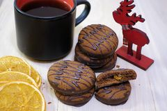 Chocolate covered cookies on a wooden table with a cup of coffee. Breakfast. Dessert stock photo