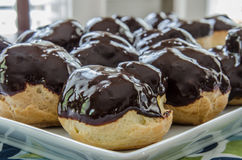 Chocolate Covered Cream Puffs. Homemade eclairs are covered with a coat of chocolate ganache stock photos