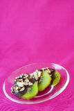 Chocolate Covered Kiwi. S on a clear plate on a pink background royalty free stock photography
