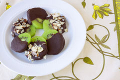 Chocolate Covered Kiwi. S on a white plate stock photo