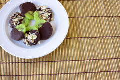 Chocolate Covered Kiwi. S on a white plate on a wooden background stock photography