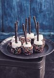 Chocolate covered marshmallows on blue royalty free stock image