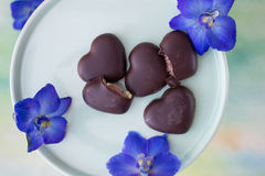 Chocolate covered marzipan hearts. Closeup of chocolate covered marzipan hearts lying on a light green plate with flowers Royalty Free Stock Photos