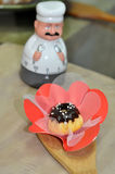Chocolate covered mini cake. In flower dish on wooden spoon with ceramic chef kitchen timer royalty free stock images