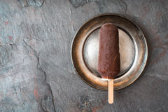Chocolate covered popsicle in the metal plate on the stone background top view. Horizontal royalty free stock image