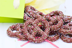 Chocolate covered pretzels. Spilling from a brightly colored bag stock images