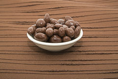 Chocolate covered raisins bowl brown background Stock Photos