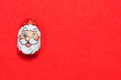 A chocolate covered with Santa Clause`s face wrapper. On a red background royalty free stock photo