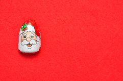 A chocolate covered with Santa Clause`s face wrapper. On a red background stock photo