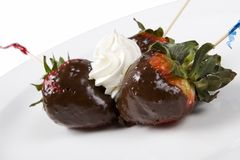 Chocolate Covered Strawberries. Three Chocolate Covered Strawberries with toothpicks on a plate Stock Photo