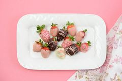 Chocolate covered strawberries for Valentine`s Day. Pretty decorated chocolate covered strawberries on a white plate for Valentine`s Day Royalty Free Stock Photos