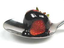 Chocolate covered strawberry. A chocolate covered strawberry on a spoon royalty free stock photography