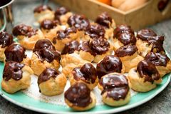 Chocolate covered vanilla cream pastry puffs close up. The chocolate covered vanilla cream pastry puffs closeup Royalty Free Stock Images