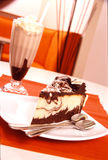 Chocolate Cream Cake with Chocolate Milkshake. With orange placemat and booth in background Royalty Free Stock Images