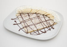 Chocolate crepe with bananas and cream. Crepe with drizzled chocolate sauce on white plate with sliced bananas and whipped cream Stock Images