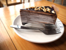 Chocolate crepe cake with almond topping in white dish on wooden. Table Stock Photos