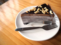 Chocolate crepe cake with almond topping in white dish on wooden. Table Stock Photo