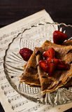Chocolate Crepes with chocolate sauce and strawberries. On a dark wooden background Royalty Free Stock Photos