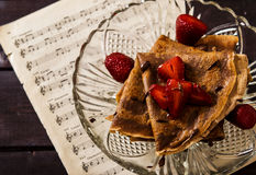 Chocolate Crepes with chocolate sauce and strawberries. On a dark wooden background Stock Photos