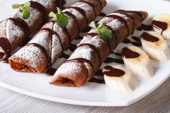 Chocolate crepes with fruit and sauce close-up. Horizontal Stock Photography
