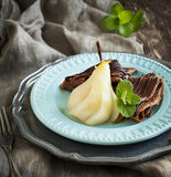 Chocolate crepes with poached pear in syrup Stock Image