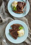 Chocolate crepes with poached pear in syrup. Chocolate crepes with poached pear served on plate Stock Photo