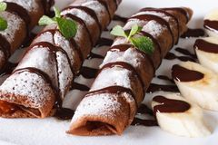 Chocolate crepes with sauce and bananas close-up horizontal Royalty Free Stock Images