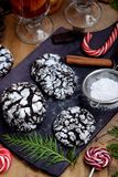 Chocolate crinkle cookies surrounded by Christmas attributes. On a wooden board Royalty Free Stock Photos