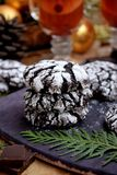Chocolate crinkle cookies surrounded by Christmas attributes. On a wooden board Stock Photos