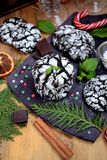 Chocolate crinkle cookies surrounded by Christmas attributes. On a wooden board Royalty Free Stock Images