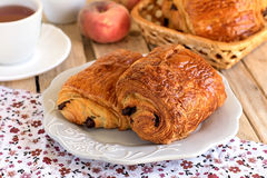 Chocolate croissants on a plate with tea for breakfast. Chocolate croissants (pain au chocolat) on a plate with tea for breakfast royalty free stock images