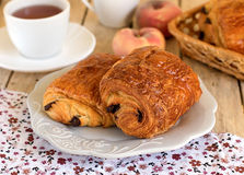 Chocolate croissants on a plate with tea for breakfast. Chocolate croissants (pain au chocolat) on a plate with tea for breakfast stock photo