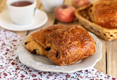 Chocolate croissants on a plate with tea for breakfast. Chocolate croissants (pain au chocolat) on a plate with tea for breakfast stock image