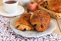 Chocolate croissants on a plate with tea for breakfast. Chocolate croissants (pain au chocolat) on a plate with tea for breakfast stock photography