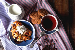 Chocolate croissants with tea and biscuits. Cup of tea, chocolate croissants, milk and oatmeal cookies are on the table Stock Images