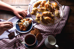 Chocolate croissants with tea and biscuits. Cup of tea, chocolate croissants, milk and oatmeal cookies are on the table Royalty Free Stock Photography